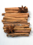 Cinnamon sticks and anise stars on white wooden background Royalty Free Stock Photography