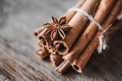 Cinnamon sticks and aniseon on the wooden surface. stock photos