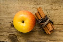 Cinnamon sticks and apple on wooden table ingredient. Cinnamon sticks and apple on wooden table food stick ingredient aroma aromatic isolated dry sweet red brown royalty free stock photography