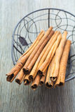 Cinnamon sticks. In a basket with wooden background Royalty Free Stock Photo