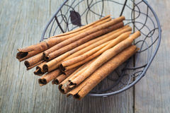 Cinnamon sticks. In a basket with wooden background Stock Photo