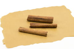 Cinnamon sticks on a brown cooking paper Royalty Free Stock Photos