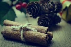 Cinnamon Sticks Bundle, Holly and Fir Cones on Oak Table - Retro Royalty Free Stock Photos