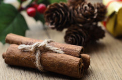 Cinnamon Sticks Bundle, Holly and Fir Cones on Oak Table Royalty Free Stock Images