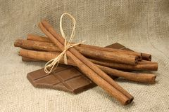 Cinnamon sticks and chocolate. On flax background Royalty Free Stock Photography