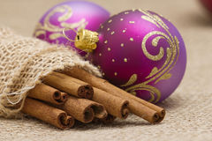 Cinnamon sticks and christmas balls Stock Photography
