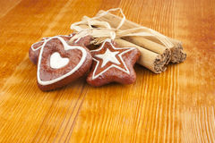 Cinnamon sticks, Christmas cookies, decoration. Cinnamon sticks and christmas cookies on a kitchen table next to a pine tree twig. Concept for Christmas baking stock photos