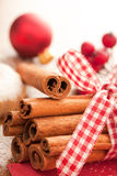 Cinnamon sticks with Christmas ornaments stock images