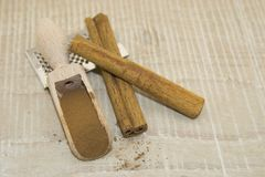 Cinnamon in a wooden spoon. Cinnamon sticks, cinnamon powder in a wooden spoon on a wooden base Stock Images