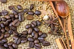 Cinnamon sticks and coffee beans close-up on sack Stock Photos
