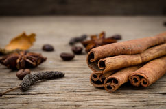 Cinnamon sticks and coffee grains on old rustic background, seas. Seasoning spice ingredients for cooking or baking Stock Photography