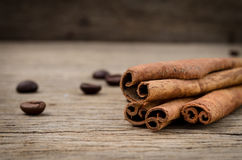 Cinnamon sticks and coffee grains on old rustic background, seas. Seasoning spice ingredients for cooking or baking Royalty Free Stock Photos