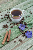 Cinnamon sticks, coffee grains, purple flower and cup coffee on old rustic green background Royalty Free Stock Images