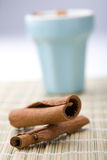 Cinnamon sticks and cup. A close-up of dry whole cinnamon sticks on a table mat with a light blue cup in the background Stock Photos