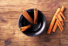 Cinnamon sticks in cup on old wooden background Royalty Free Stock Images