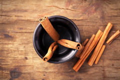 Cinnamon sticks in cup on old wooden background. Stock Photos