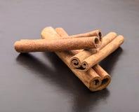 Cinnamon sticks on drak table Royalty Free Stock Photos
