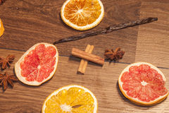 Cinnamon sticks, between dry fruits and season. On wooden background Stock Photography