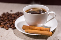 Cinnamon sticks in focus beside hot coffee Stock Photo
