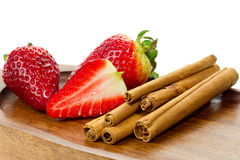 Cinnamon sticks and fresh stawberries Stock Images