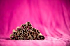 Cinnamon sticks on fuchsia canvas background. A pile of cinnamon sticks on fuchsia canvas background Stock Images