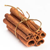 Cinnamon sticks with gold ribbon. Cinnamon sticks with gold Christmas ribbon on white isolating background Stock Photo