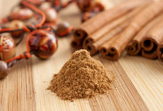 Cinnamon sticks with ground cinnamon and beads Royalty Free Stock Image