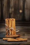 Cinnamon Sticks. A group of cinnamon sticks tied into a bundle with natural jute string and standing on end with three sticks loose in front of bundle on rustic Royalty Free Stock Photography