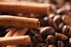 Cinnamon sticks laying above brown coffee beans Royalty Free Stock Photography