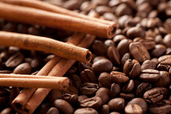Cinnamon sticks laying above brown coffee beans Royalty Free Stock Images