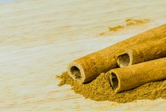 Cinnamon sticks laying on cinnamon powder. Closeup of three cinnamon sticks laying on cinnamon powder on a wooden cutting board Royalty Free Stock Photos
