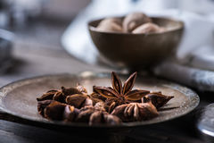 Cinnamon sticks, nutmeg and anise stars in cups over dark scorched wooden background. Anise stars on plate and nutmeg in bowl over dark scorched wooden Royalty Free Stock Images