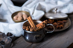 Cinnamon sticks, nutmeg and anise stars in cups over dark scorched wooden background. Selective focus, horizontal composition Royalty Free Stock Photography