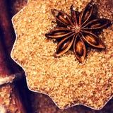Cinnamon sticks, nuts and star anise on brown sugar, macro. Baki Royalty Free Stock Photos