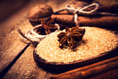 Cinnamon sticks, nuts and star anise on brown sugar, macro. Baki Royalty Free Stock Images