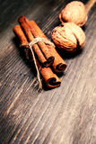 Cinnamon sticks  and nuts on  wooden background. Christmas winte Stock Photos