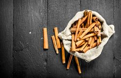 Cinnamon sticks in an old bag. On a black wooden table Royalty Free Stock Image