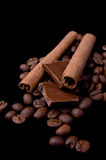 Cinnamon sticks over coffee beans and chocolate Stock Photos
