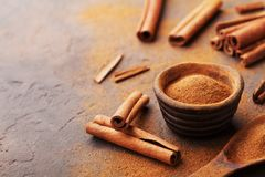 Cinnamon sticks and powder on brown rustic background. Aromatic spices. Stock Image