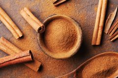 Cinnamon sticks and powder on brown rustic table top view. Aromatic spices. Stock Photo
