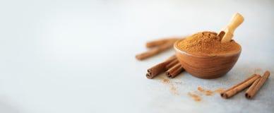 Cinnamon sticks and powder on grey background. Spices for ayurvedic treatment. Alternative medicine concept stock image