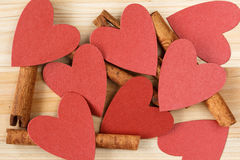 Cinnamon sticks and red hearts on a wooden background Stock Photography