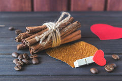 Cinnamon sticks with roasted coffee beans decorated with hearts and cloth pin on wooden planks St.Valentine's Royalty Free Stock Image