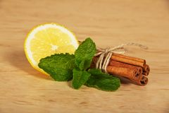 Cinnamon sticks, segment of a lemon and mint Royalty Free Stock Photography