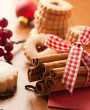 Cinnamon sticks with some cookies and berries. On a table Stock Photography