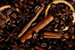 Cinnamon sticks, star anise, coffee beans and dried orange on the kitchen table. Fragrant spices for coffee drink, close-up stock photo