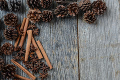 Cinnamon sticks, star anise and pine cones on rustic wood Stock Photo