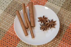 Cinnamon sticks with star anise. On white saucer royalty free stock image