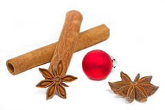 Cinnamon sticks with star aniseed. And red christmas ball Royalty Free Stock Photo
