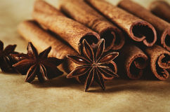 Cinnamon sticks and three stars anise on brown paper background Royalty Free Stock Images